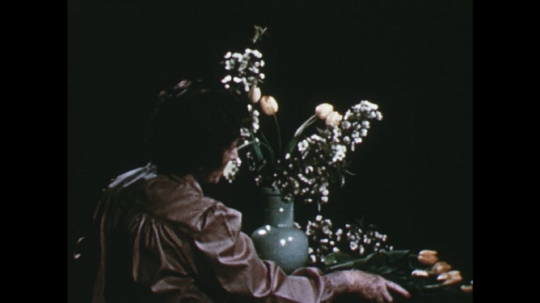 UNITED STATES: 1960s: lady adds tulips to arrangement.