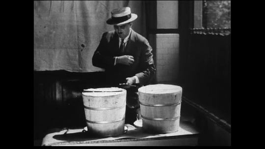 UNITED STATES 1930s: Medium shot of suited man inspecting butter  in buckets. Medium shot of shopkeeper setting-up price signs on buckets of butter.