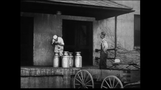 UNITED STATES 1930s: Wide shot of dockworker or customer observing milkman sniff inspecting lids of milk cannisters cuts to medium shot of worker.