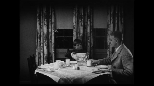 UNITED STATES 1930s: Medium wide shot of family sitting down at table to eat and discovering the milk is bad.