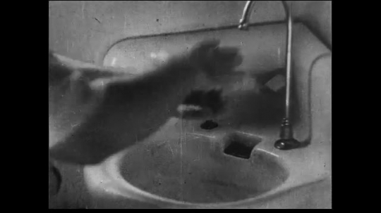 UNITED STATES 1930s: Close up of man drying hands over sink crossfades with medium wide shot of man donning clean suit.