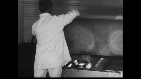 UNITED STATES 1930s: Medium close up of man putting milk cans into freezer. Close up of buckets being scrubbed.