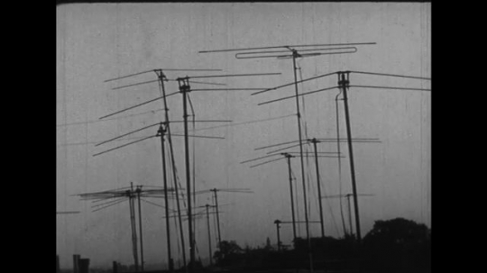 UNITED STATES 1930s: Television antennas stand atop houses as actor Milton Berle acts.