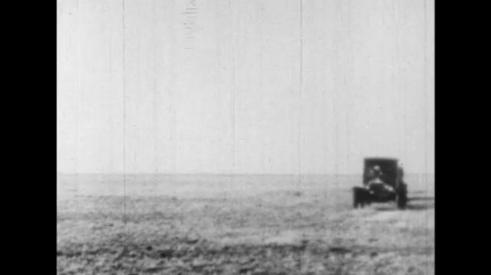 UNITED STATES 1930s: Cars drive through a range and park.