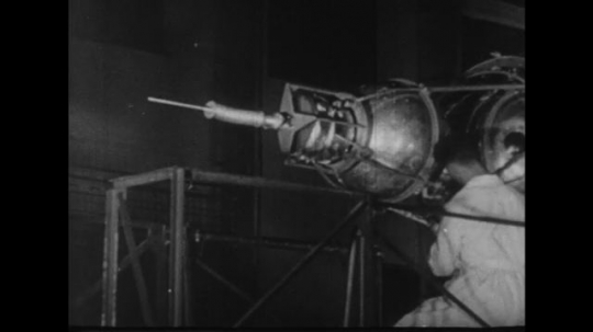 UNITED STATES 1950s: Scientist working on satellite / Nosecone put into place.