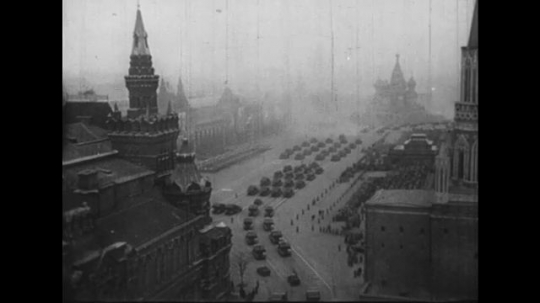 UNITED STATES 1950s: Long shot of Moscow / Tank pulls rocket / Rocket pulled down street, crowd waves / Joseph Stalin waves from balcony / High angle view of rockets on street.