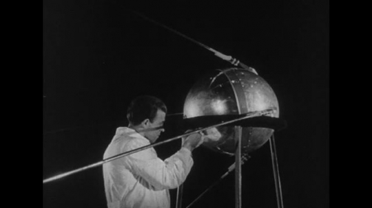 RUSSIA 1950s: A scientist works on a satellite as Soviet Union leader Khrushchev discusses plans.