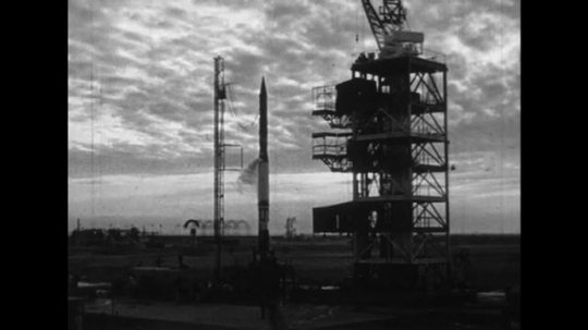 UNITED STATES 1950s: A rocket starts to get smoke as it stands next to a launch pad.