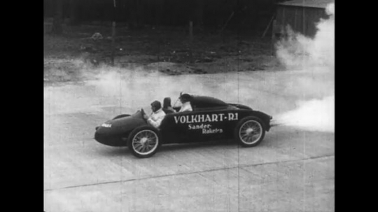 UNITED STATES 1950s: A race car is photographed as it speeds and leaves the audience in its dust.