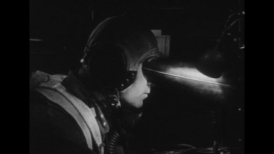 UNITED STATES 1940s: Soldier looks through viewer / Close up of radar screen / Aerial view of plane / Soldier looks through viewer / Radar screen / Bombardier with bomb sight.