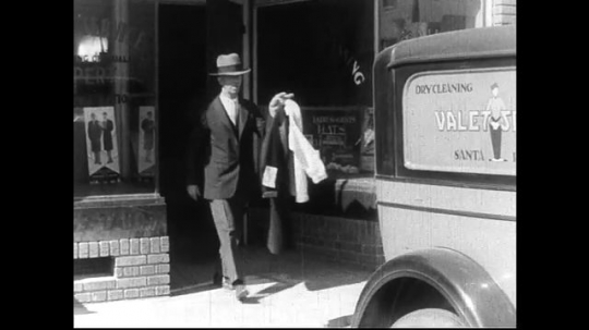 SANTA PAULA- CIRCA 1929: Dry cleaning workers load the back of a delivery car, labeled