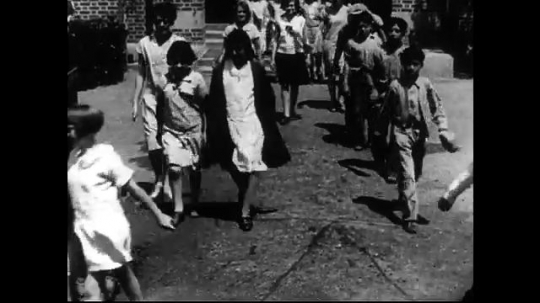 SANTA PAULA- CIRCA 1929: A large group of elementary school aged children exit a school building and school yard.