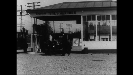 SANTA PAULA- CIRCA 1929: Pan across parking lot of autobody maintenance shop. A gas station attendant fuels a car while another wipes the car