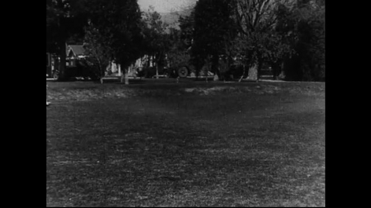 SANTA PAULA- CIRCA 1929: Young women run through a park and into the center frame of a camera, where they group together as if preparing to take a photograph.