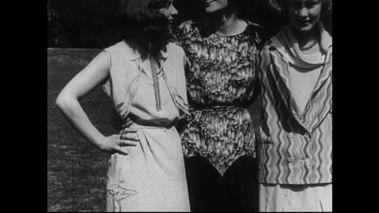 SANTA PAULA- CIRCA 1929: a medium-close up shot pans across a group of women who pose together in a park.