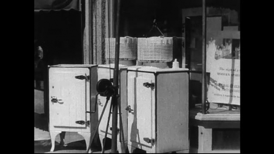 SANTA PAULA- CIRCA 1929: Three cabinets sit on the sidewalk outside of a business.  A man walks by them,