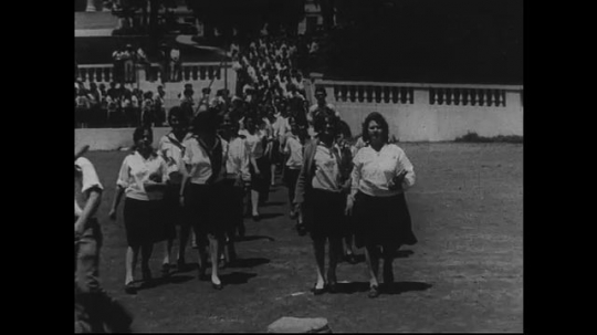 SANTA PAULA- CIRCA 1929: Over one hundren high school aged students descend the steps to their school's lower courtyard and walk toward the camera, breaking on either of its sides.