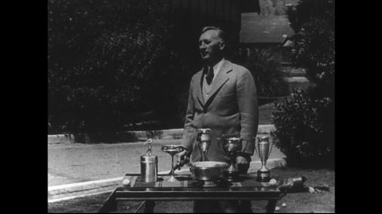 SANTA PAULA- CIRCA 1929: A man with a golf club stands in a yard, posing behind a table on which his golfing trophies sit.  He demonstrates putting.  The ball rolls into a hole.