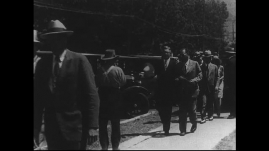 SANTA PAULA- CIRCA 1929: A group, made almost entirely of men, walks down a sidewalk in business wear.  Some also wear hats and smoke cigars.  A few men acknowledge the camera as they walk by it.
