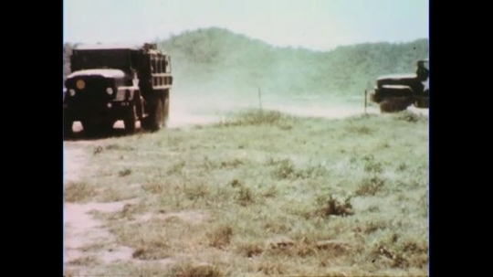 VIETNAM 1960s: Army trucks filled with soldiers pull up and stop.
