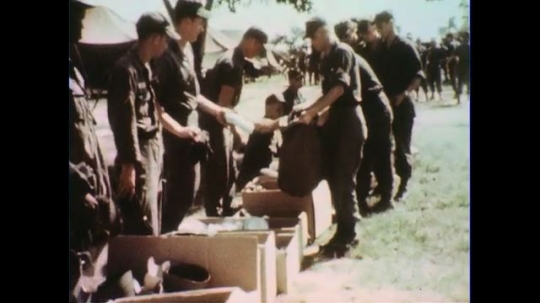 VIETNAM 1960s: Line of soldiers receive items / Soldiers get guns, sign paper.