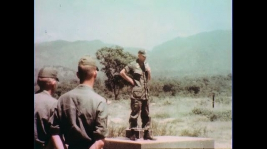 VIETNAM 1960s: Officer speaks on platform, soldiers in foreground.