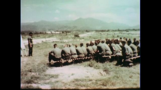 VIETNAM 1960s: Long shot, officer speaks to seated soldiers.