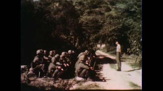 VIETNAM 1960s: Officer speaks to seated soldiers.