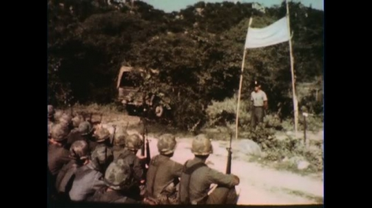 VIETNAM 1960s: Officer speaks to seated soldiers, grabs sign pole / Soldiers sitting.