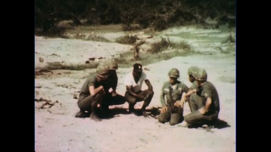 VIETNAM 1960s: Soldiers and officer kneel with mine, officer gives instructions.