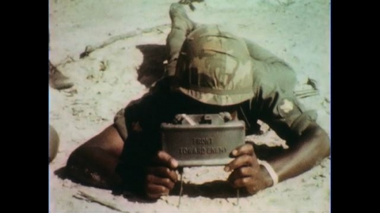 VIETNAM 1960s: Soldier with landmine, soldier twists fuse / Soldier with wire, attaches to mine.