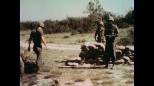 VIETNAM 1960s: Soldiers walk to bunker / Officer gives detonator to soldier / Close up, hands with detonator / Soldiers kneel behind bunker.