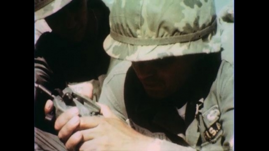 VIETNAM 1960s: Close up, soldier presses detonator / Explosion / Close up, officer bites head off chicken, zoom out / Seated soldiers / Officer speaks to soldiers / Seated soldiers.