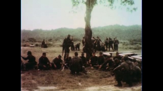 VIETNAM 1960s: Long shot, seated soldiers / Pan of soldiers applying camouflage / Medium shot / Close up, soldiers apply camouflage.