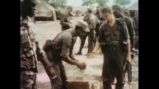 VIETNAM 1960s: Soldier hands gun clips to soldier, tilt down to backpack / Soldier gives instruction to other soldier / Soldier adjusts gun on other soldier