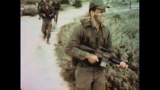 VIETNAM 1960s: Tracking shot, soldier marches with gun / Soldiers march toward camera.