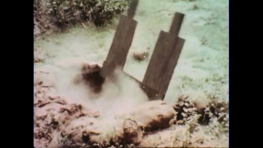 VIETNAM 1960s: Explosion in booby trap / Soldiers turn, fire guns / Soldiers dive on ground.