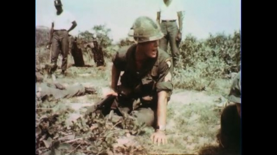 VIETNAM 1960s: Officer kneeling on ground, give orders, soldiers crawl to officer.