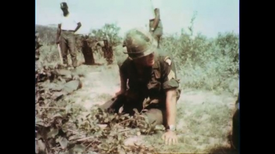 VIETNAM 1960s: Officer kneeling on ground, give orders, soldiers and officer stand.
