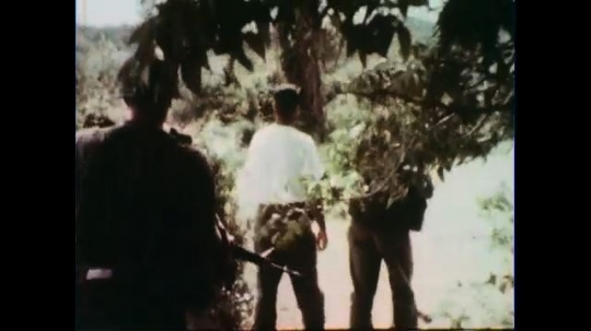 VIETNAM 1960s: Hand held shot, soldier and officer walking from behind.