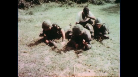 VIETNAM 1960s: Soldiers on ground, soldiers stand and walk.