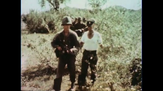 VIETNAM 1960s: Soldiers walk toward camera, turn, fire into bushes / Long shot, zoom in on soldiers in bushes / Zoom in on officer.