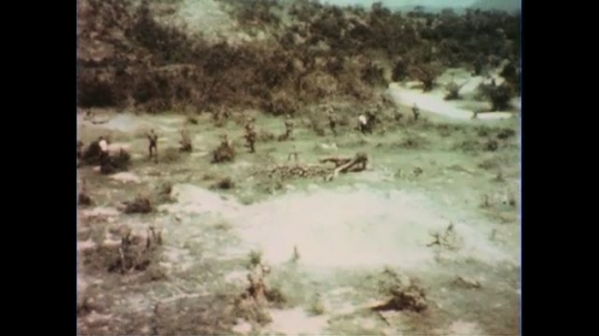 VIETNAM 1960s: Aerial tracking shot, soldiers fire guns, move through bushes.