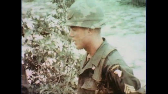 VIETNAM 1960s: Close up of officer, pan to soldiers / View of soldiers and officer.