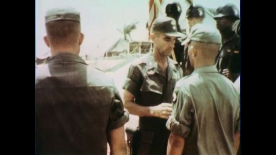 VIETNAM 1960s: Officer pins badge on soldier, shakes hand.