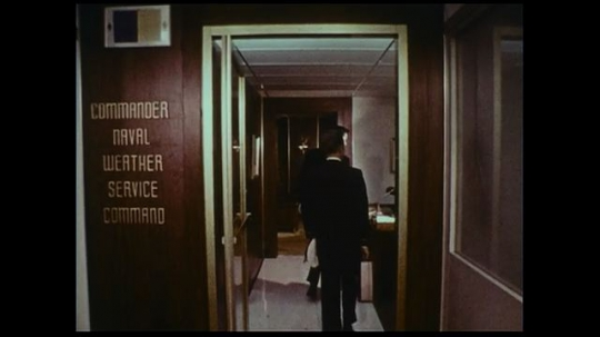 UNITED STATES 1970s: A man enters the office of the United States Naval Weather Service Command.
