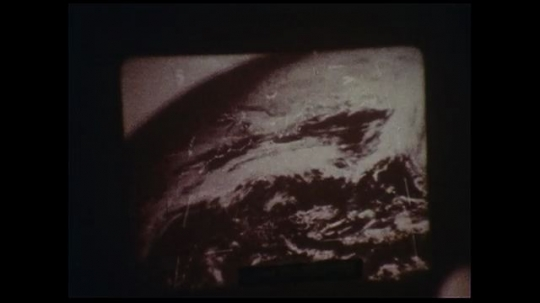UNITED STATES 1970s: Men observe satellite videos of swirling clouds.