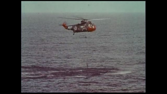 UNITED STATES 1970s: A helicopter stays suspended in the air as a map shows different areas of water with their corresponding wave readings.
