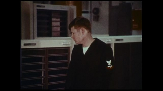 UNITED STATES 1970s: A naval officer checks computer data at a naval fleet numerical weather center.