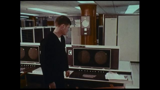 UNITED STATES 1970s: A naval officer  views the data recorded by computer at the naval fleet numerical weather center as they appear on the different computer screens.